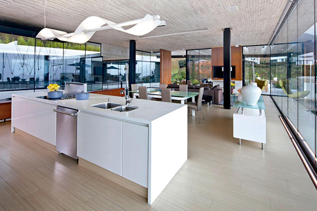 El mesón de la cocina,  de Corian blanco e iluminado por una lámpara colgante  con difusor ondulante opalizado, domina por completo el ambiente del comedor y la sala.