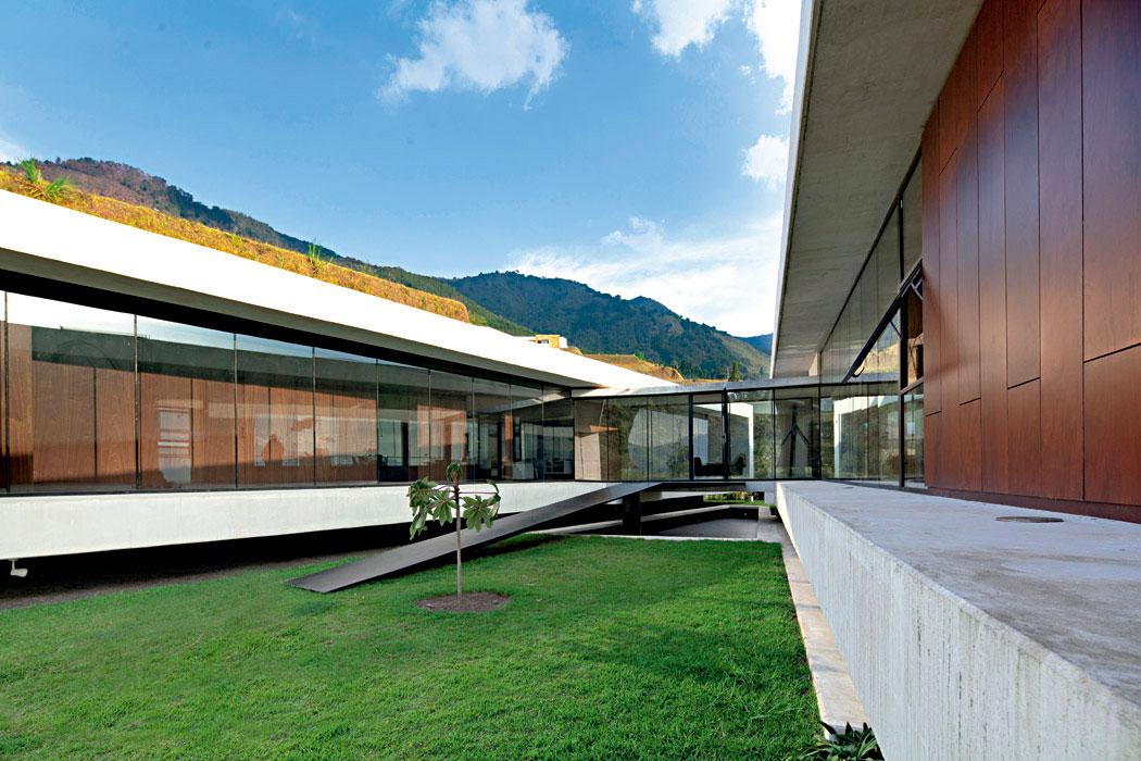 El volumen social y el ala de habitaciones se abren como una tijera para dar lugar a un patio en el que crece un guayacán.