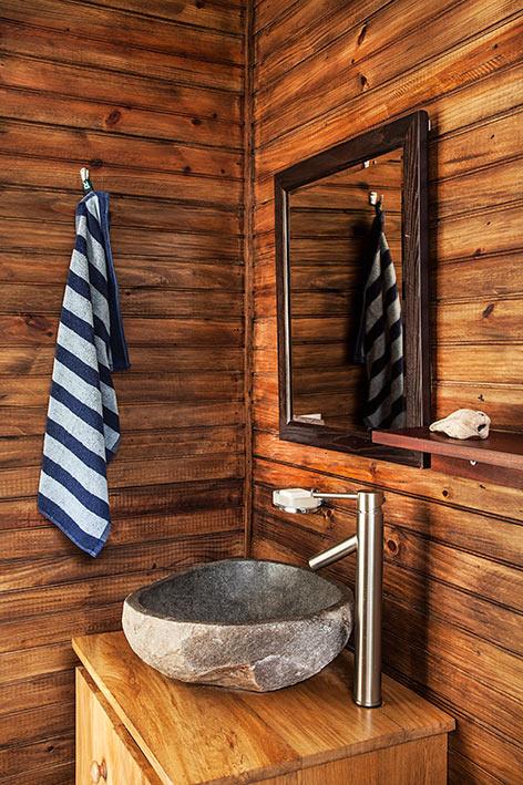 El cedro del marco del espejo contrasta con la pared, la repisa y el mueble, para hacer un juego de maderas acompañado de la grifería de acero inoxidable y el lavamanos de piedra.