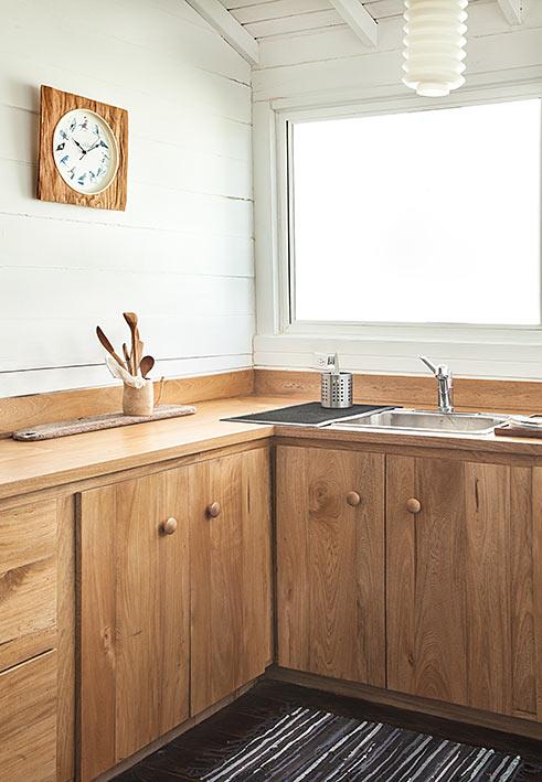 El reloj de la cocina, importado de Nueva York, tiene un marco de papel con estampado de madera que puso la propietaria.  Su textura y color combinan con el mueble y el tazón de bambú que reúne las cucharas de palo. El lavaplatos es de acero inoxidable.