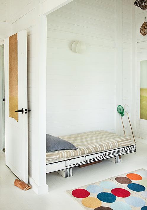 Izquierda. El tapete de Ikea le aporta color y calidez al segundo piso de la casa, en el que predomina el blanco  en las paredes. La cama sencilla, ubicada cerca del televisor,  está hecha en madera sintética.