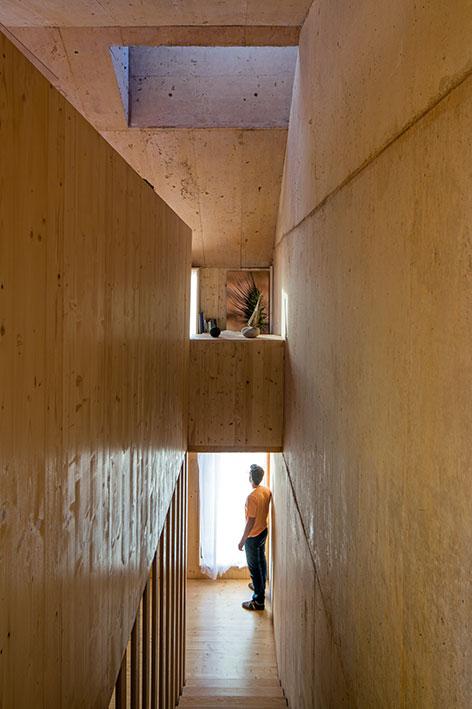 La calidez de los espacios interiores, donde predomina el uso de madera, contrasta con la abstracción y dureza material del exterior.