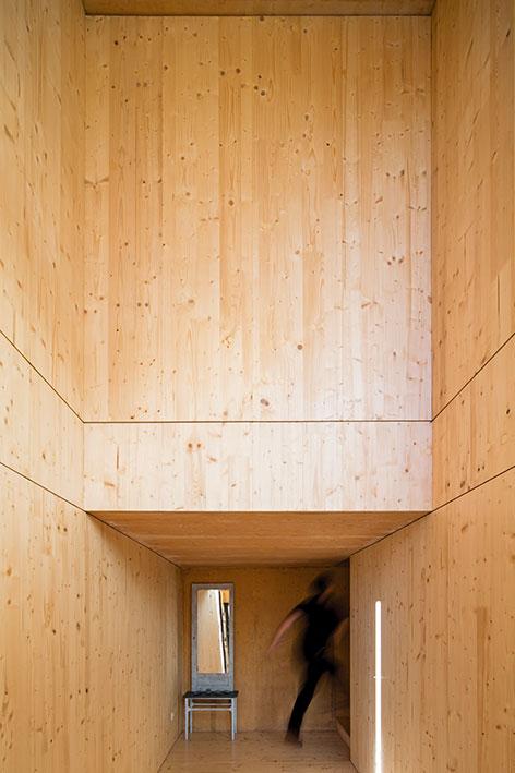 En claro contraste con el frío muro de hormigón exterior, el hall está enchapado completamente en madera. Las placas, que originalmente sirvieron para darle forma al muro, fueron reutilizadas como terminación.