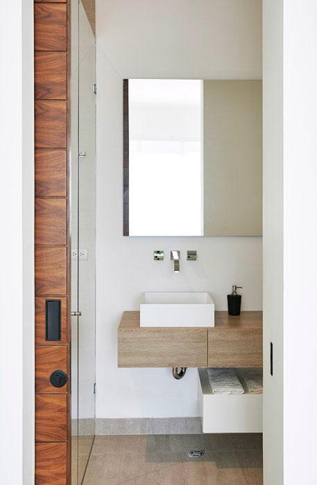 Para aprovechar al máximo el espacio en el baño auxiliar emplearon prácticos cajones y un sencillo espejo que aporta profundidad.