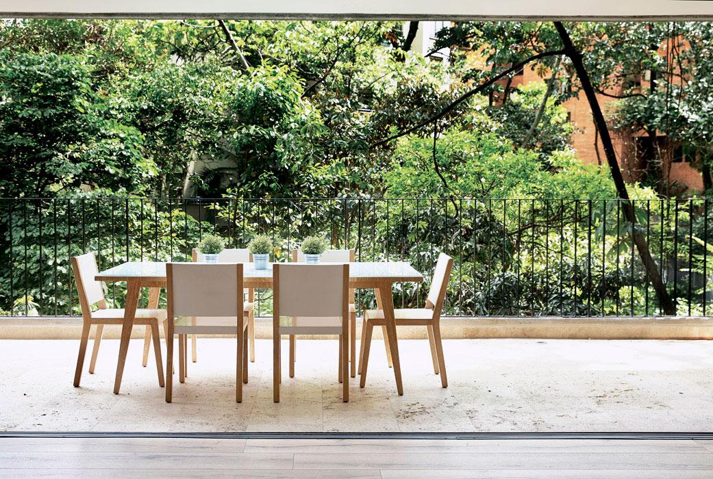 La terraza, de 30 metros cuadrados, se integra al área social y permite disfrutar del entorno natural que rodea al apartamento. La mesa y las sillas, de CCV Taller y Diseño,  son de chapilla de roble europeo; la primera tiene un vidrio pintado con una película blanca que resalta el carácter práctico y moderno del diseño.