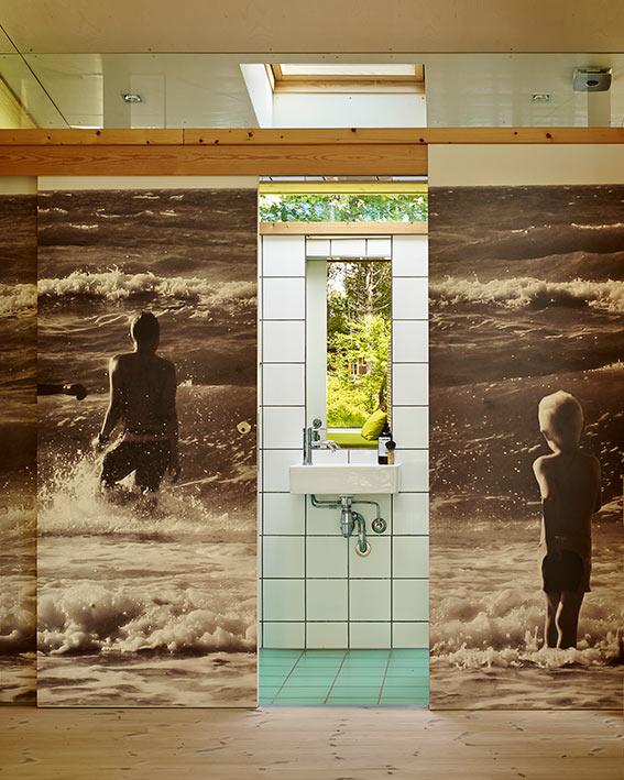 Tras este mural, que muestra en la playa a los hijos del propietario, está oculto el baño, donde predomina el blanco a juego con la temática natural de la vivienda.