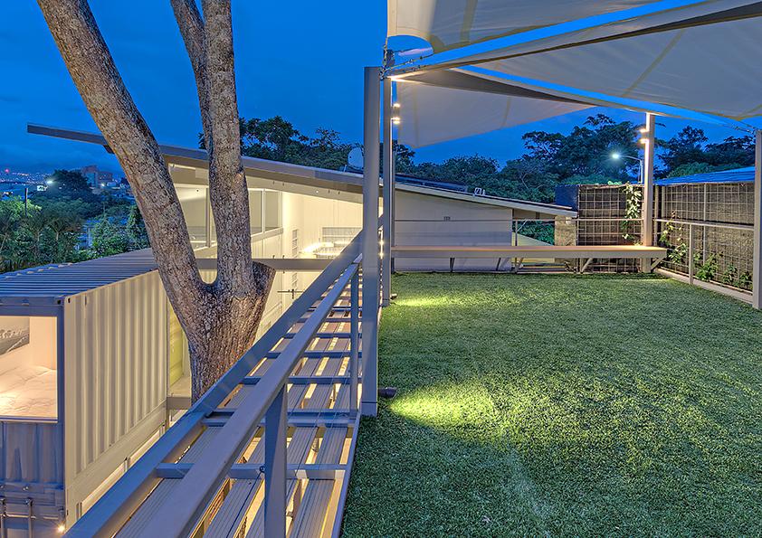Una pasarela exterior conduce a las escaleras que conectan con la azotea del tercer nivel. La piel de bambú en su fachada noroeste se compone de paneles móviles de Bambutico que protegen los espacios interiores de la radiación solar. El cedro original del terreno desempeña un papel muy importante para la disposición de la vivienda en el lote, de tal manera que exista contacto visual hacia el árbol desde cualquier punto de la casa.
