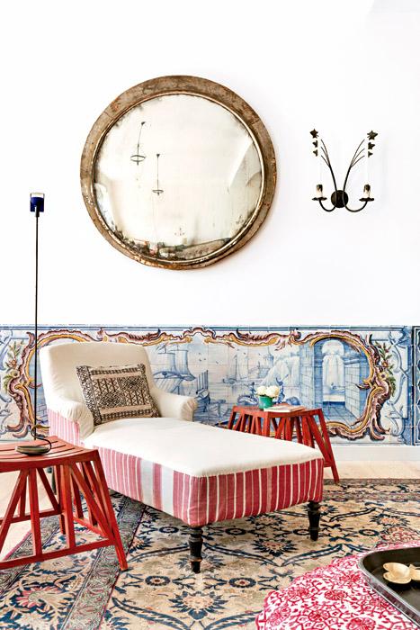 Los espejos redondos del salón provienen de una estación de tren de Polonia y fueron comprados en Bruno, un anticuario en la calle Clignancourt, en París. La gran alfombra en tonos azules es persa, adquirida en Christie's Londres. La chaise longue es francesa y está tapizada con gruesos y antiguos tejidos de ropa de cama y un tejido de la India con rayas rojas y blancas. El almohadón con estampado geométrico negro es de Mustapha Blaoui, en Marruecos. Las banquetas rojas a su lado proceden de Egipto.
