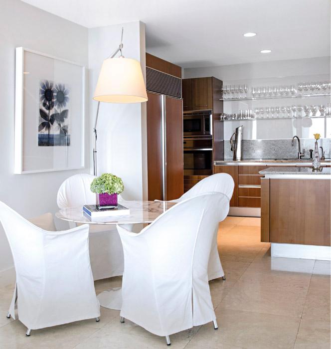 La cocina abierta, moderna y funcional se comunica con un práctico comedor auxiliar del diseñador estadounidense Eero Saarinen. Las sillas son de Philippe Starck. La lámpara de piso es la clásica Tolomeo, de Artemide. Sobre la pared, un dibujo de David Manzur.