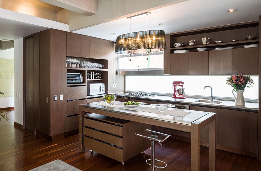En esta moderna cocina abierta la atención la captura la delicada lámpara con pantalla de velo y cristales en su interior, importada de Alemania. La isla del centro es móvil, al igual que el mueble debajo de ella, lo que le da versatilidad al espacio.
