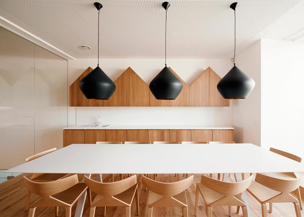 La madera del mobiliario y las lámparas de techo oscuras contrastan y se complementan en este espacio.