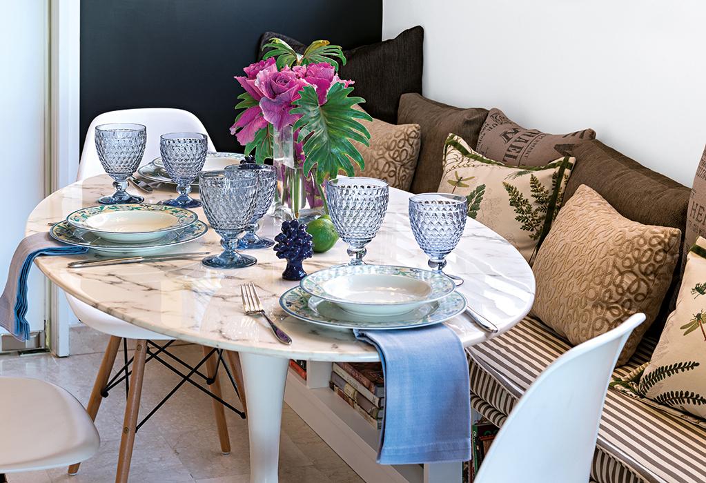 Una mesa Tulip de mármol blanco, diseño del arquitecto y diseñador estadounidense de origen finlandés  Eero Saarinen, y una banca hecha  en mampostería, con cojines tapizados con telas de Michel Editores, conforman el comedor diario en la cocina.