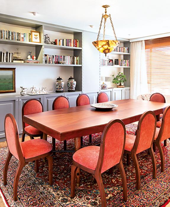 La mesa del comedor principal, de madera maciza, la compraron los dueños en un anticuario de Bogotá.  Las sillas, tapizadas en una tela color coral, combinan con el mueble empotrado en la pared. La lámpara de techo, de un anticuario de Miami, proyecta una iluminación sutil y elegante.