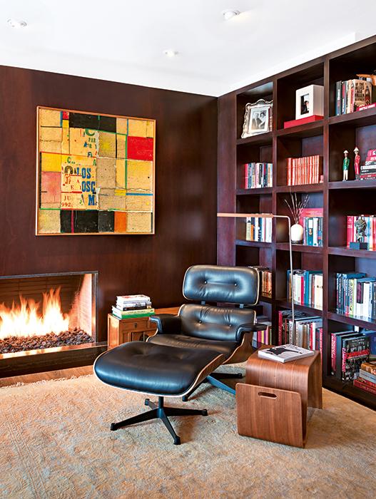 La Eames Lounge Chair y la chimenea de gas dan la bienvenida al estudio contiguo  a la sala. Este rincón apacible  es uno de los lugares favoritos  de su dueño para leer. Un revistero de una sola pieza de madera, en el que está un libro del artista del street art británico Banksy, revela parte de la variedad de libros que hay  en este apartamento.
