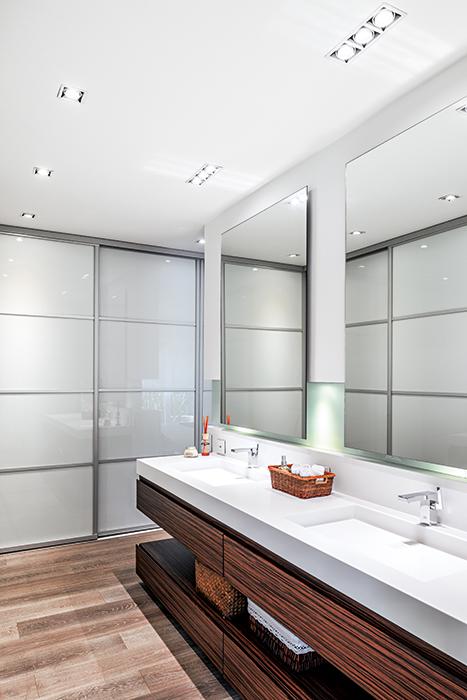 El baño principal tiene un mesón hecho en Corian, material sintético que sobresale al no presentar uniones, y la madera es la misma utilizada en la biblioteca para dar uniformidad a la remodelación. La iluminación del nicho permite separar visualmente los espejos  de la pared, esto genera más volumen.