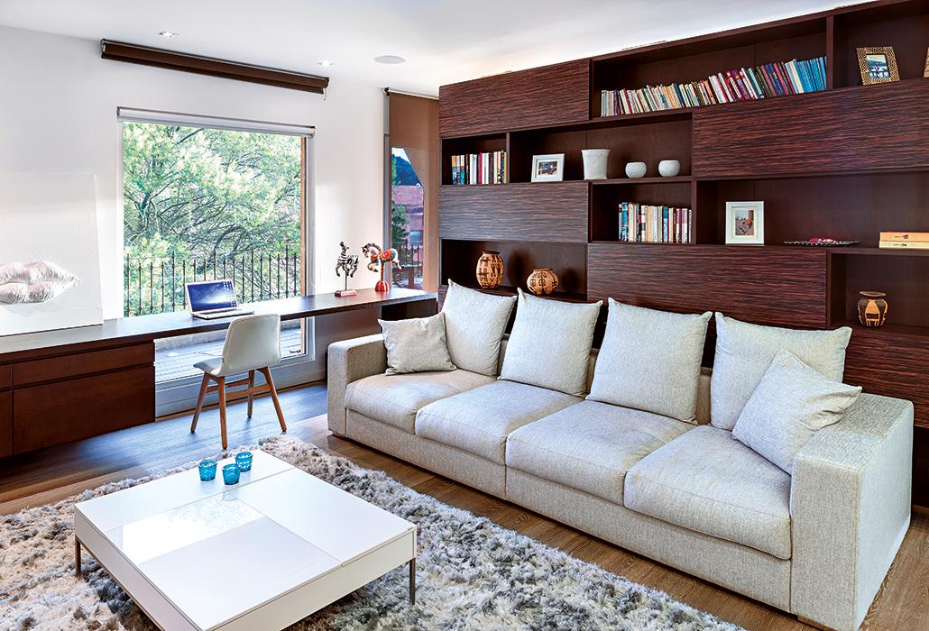 Los Solar Screen negros son empleados para proteger los muebles del sol. La biblioteca que separa el estudio de la sala se desplaza para crear un solo ambiente.