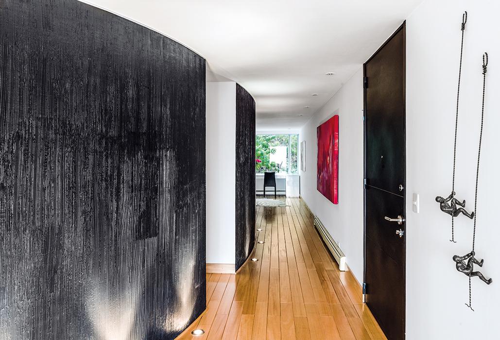 """Recorrido Escultural. Las paredes blancas contrastan con el muro curvo color gris oscuro brillante, al cual le dieron un terminado de cepillado vertical al estuco. Esto, junto a la iluminación proveniente del piso, crea un efecto de mayor altura y da un aspecto escultural al muro.  La arquitecta afirma que """"lo más importante en una remodelación es que el espacio sea el resultado de un proceso racional y funcional en conjunto con los dueños, de cómo ellos quieren vivir y sus necesidades. Nunca puede ser un capricho solo estético""""."""