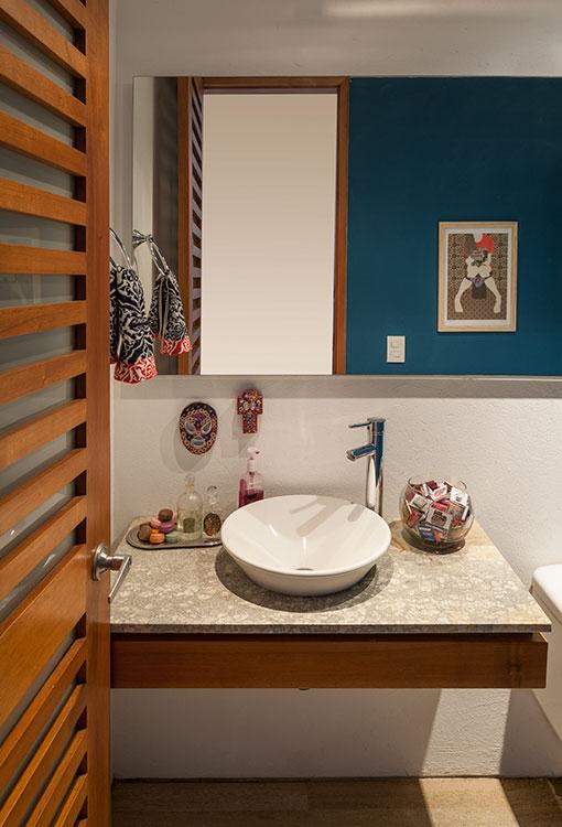 En el baño social hay una cruz mexicana y una máscara de lucha libre con flores reales sostenidas con resina. Un bowl contiene una colección de fósforos de la propietaria. Al lado del lavamanos se aprecia una bandeja con antiguos botellones de vidrio y varios jabones en forma de macarrón del almacén Pas de Deux. Sobre la pared azul, que la propietaria cambia periódicamente de color, se destaca una obra de la artista Gabriela Sánchez.