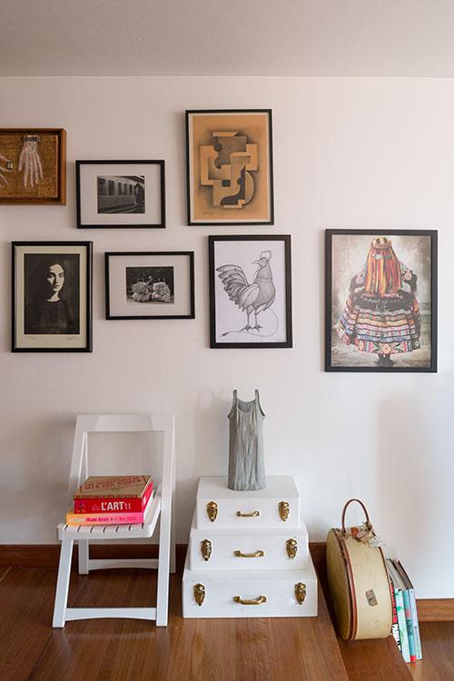 La silla pertenecía al comedor auxiliar de la madre de la propietaria y la pintaron de blanco para darle un aspecto moderno. Al lado hay tres maletas antiguas, que sostienen una escultura, y una sombrerera heredada por la dueña. Arriba, un dibujo de un gallo de León Trujillo, varias fotografías y una pintura de estilo cubista realizada por la abuela de la propietaria.
