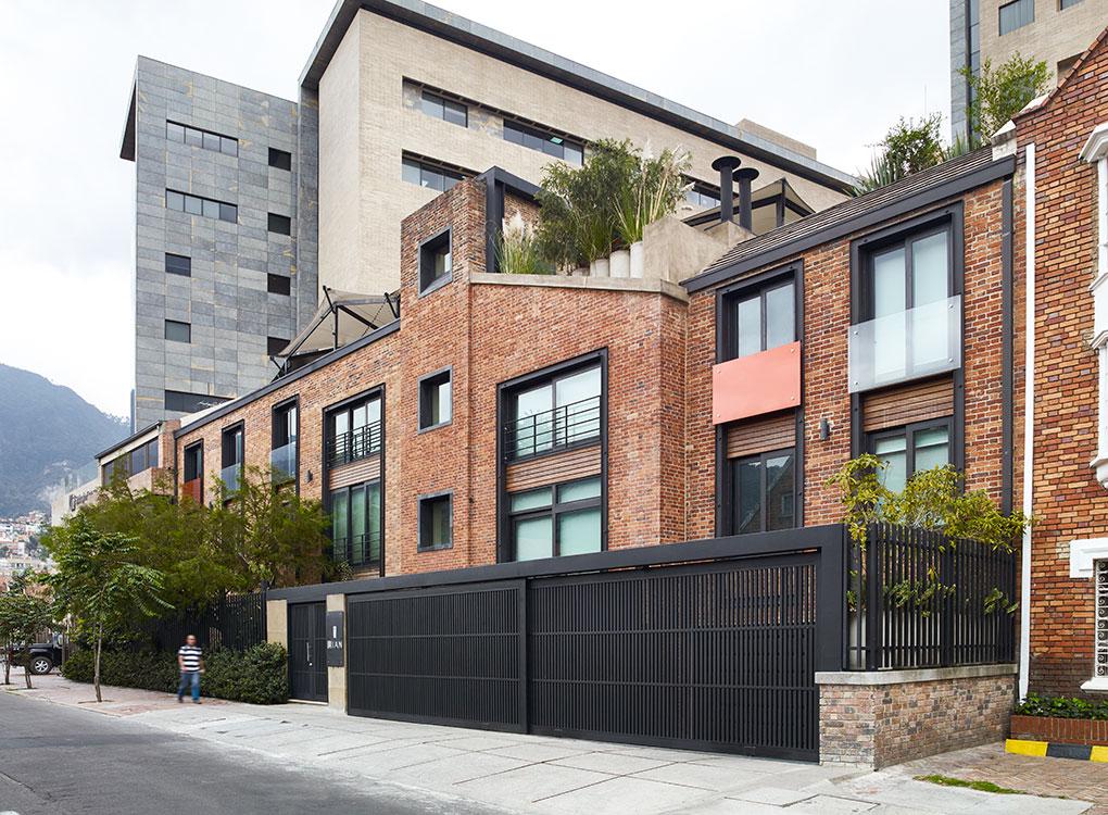 Aunque comparte el color y la textura del ladrillo, la fachada de ritmo variado y elementos casuales se adapta a la modulación y a la escala de las casas del barrio.