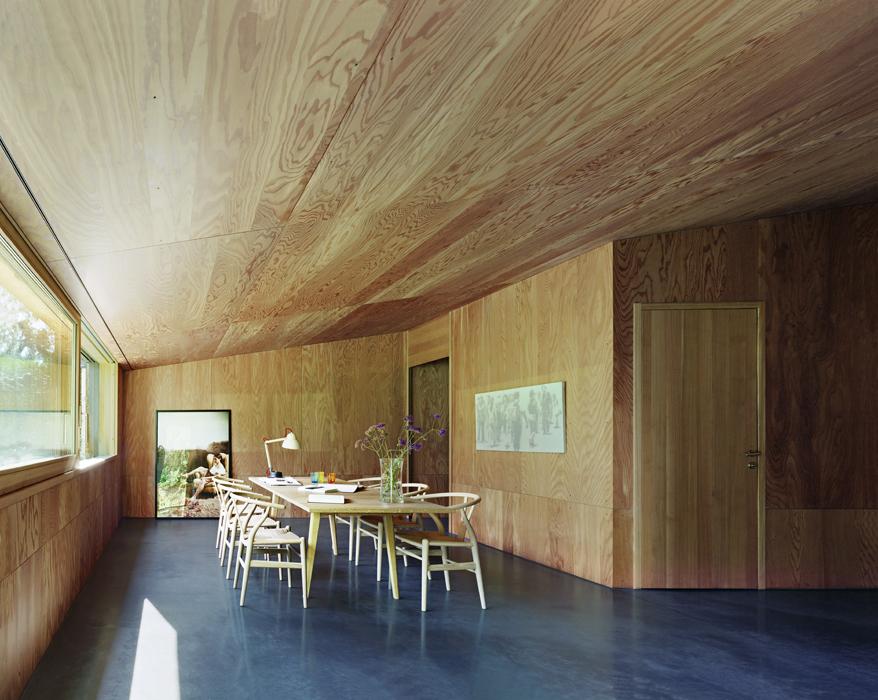 El comedor de la casa 26 rodeado de madera y con el toque clásico de las sillas Wishbone, un diseño de Menta Group en Suiza. Foto: James Silverman.