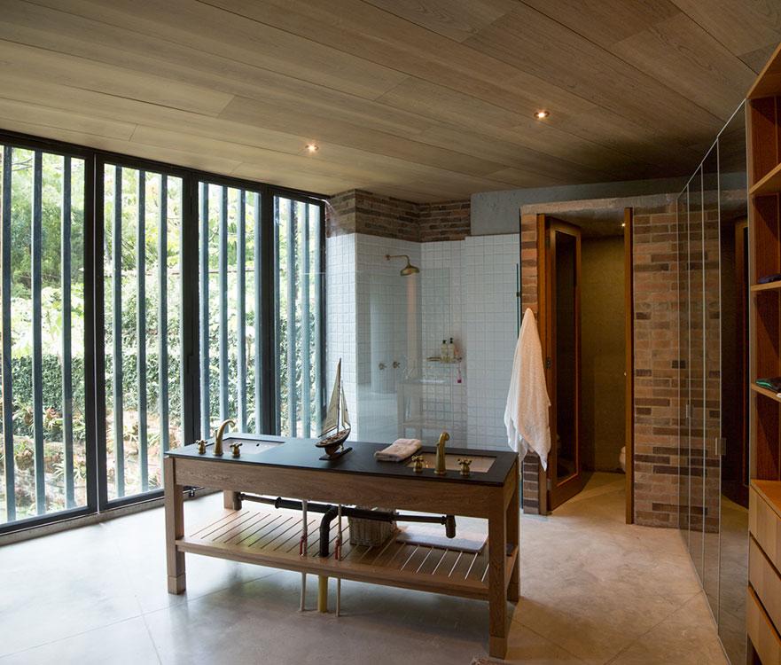 Al  natural  La luz y el verde de la montaña entran directamente al baño, diseñado por ALH Taller de Arquitectura, y se reflejan en las puertas de espejo de los armarios. El mesón de madera en isla muestra las tuberías con audacia y honestidad, y los materiales –enchape cerámico de 12 x 12 cm, concreto a la vista, ladrillo y madera– expresan su naturaleza sin reservas. Cubículos separados para la ducha y el sanitario facilitan