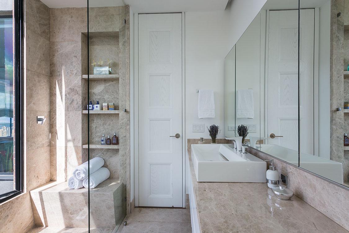 Ambiente  único  Ubicado en un piso 22, la privacidad permite tener en la ducha una ventana de piso a techo que inunda de luz el baño diseñado por el arquitecto Carlos Moreno, enchapado en mármol Emperador. La claridad se refleja en las láminas de espejo, que cierran los gabinetes, en el blanco de los muros y los muebles sanitarios, y en la grifería Hansgrohe. El vidrio divisorio es fijo y los nichos de la ducha permiten mantener ordenado el espacio.