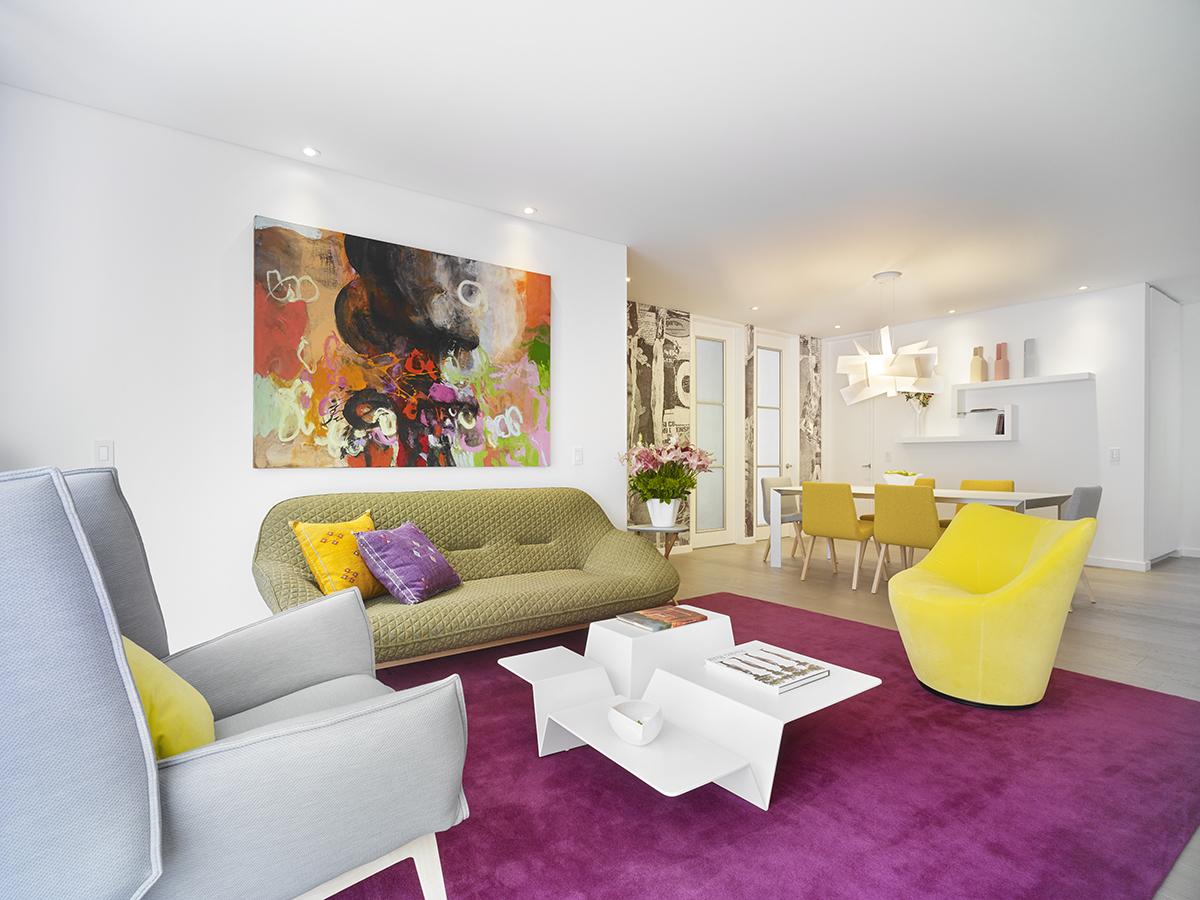 La sala, enmarcada por  el tapete, se integra con la cocina abierta, donde el blanco predomina. Las lámparas de techo son las Pharaoh, diseño  de la firma Studio Catoir.