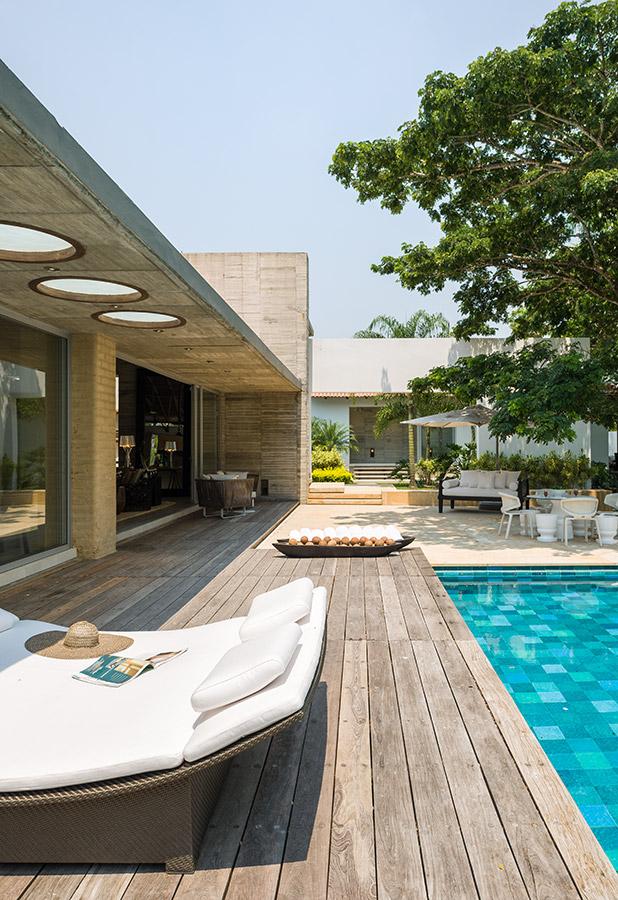 Un deck de teca extiende la zona social hacia la piscina, enchapada en baldosas cerámicas en tres tonos de azul. Los planos de concreto están combinados con las cubiertas inclinadas para darle variedad a la arquitectura.
