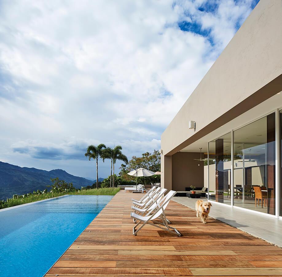 El deck frente a la piscina –al igual que en las demás terrazas exteriores– está enchapado en porcelanato tipo madera, cálido, natural y antideslizante, perfecto para el uso en este tipo de contexto.
