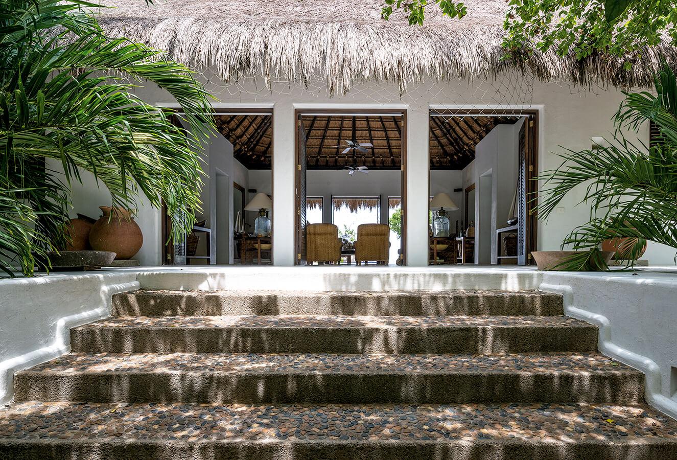 Al cobijo de una gran cubierta de palma vendeaguja aparece un salón que se abre al entorno. El mobiliario y los objetos responden a una estética que se sintoniza con la cultura material de la región.