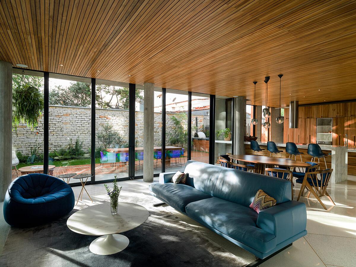 La continuidad del espacio en el salón-comedor-cocina permite una constante interacción entre los ambientes interiores y la vegetación y la luz proveniente del exterior.