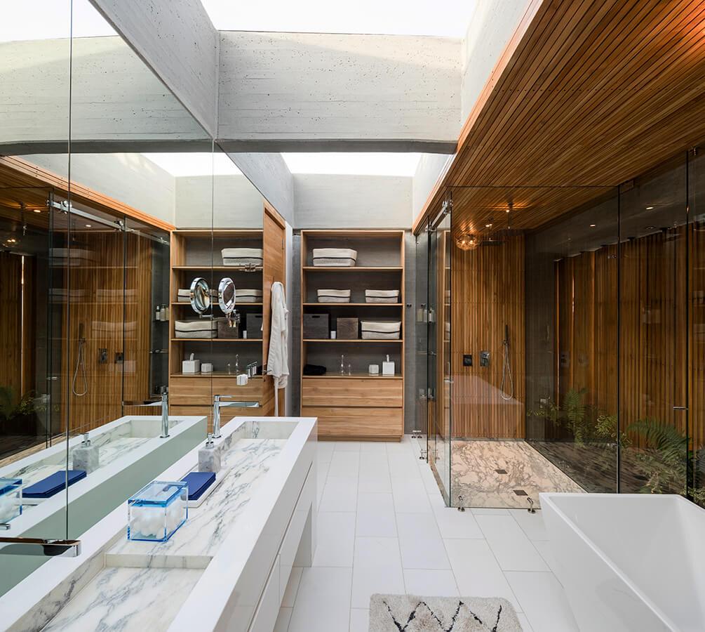 El baño principal continúa con la paleta de materiales del resto de la casa, otorgando el protagonismo a la luz, la naturaleza y la madera.