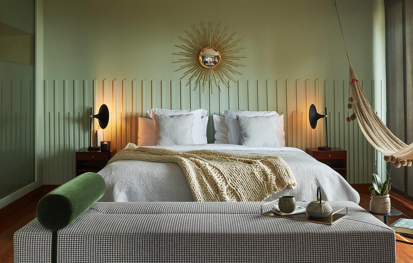 Para mantener la continuidad con la gama cromática de la cama, el equipo de diseño  de Folies creó in situ un espaldar de cama asimétrico de gran formato, hecho con listones de madera pintados de verde menta. Sobre él, resalta el espejo Sol, de Folies. A su alrededor, elementos como las lámparas metálicas de escritorio Trompeta, de Diamantina y La Perla y unas mesas de noche vintage cierran este espacio compartido.