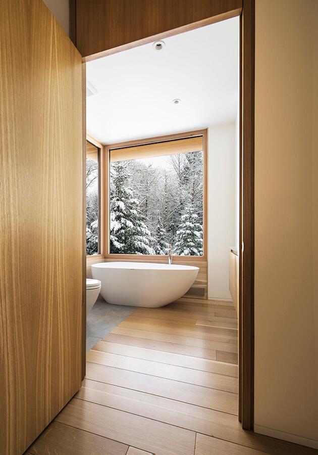 El uso de una paleta de materiales limitada (cedro blanco, concreto pulido, aluminio negro y vidrio) tanto dentro como fuera ayuda a borrar los límites entre la arquitectura y la naturaleza en esta casa diseñada por el estudio de arquitectura YH2. Fotografía: David Marien-Landry.